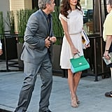 Amal's white pleated Chanel dress is a vintage piece that she styled with a Dolce & Gabbana colorblock bag for a cool kick.