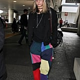 Cara Delevingne stayed warm and comfortable in a knit beanie and rainbow-colored pants.