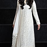 Wearing a white lace Indian outfit with ankle-strap heels.
