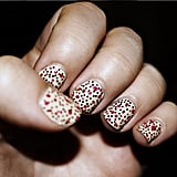 A base coat of American Apparel lacquer in California Trooper is covered with pink dots (Essie Bermuda Shorts) and Sally Hansen's black nail art pen.