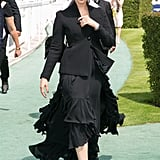 Opting for a monochrome look in a black ruffled dress, tailored blazer, and a hat.
