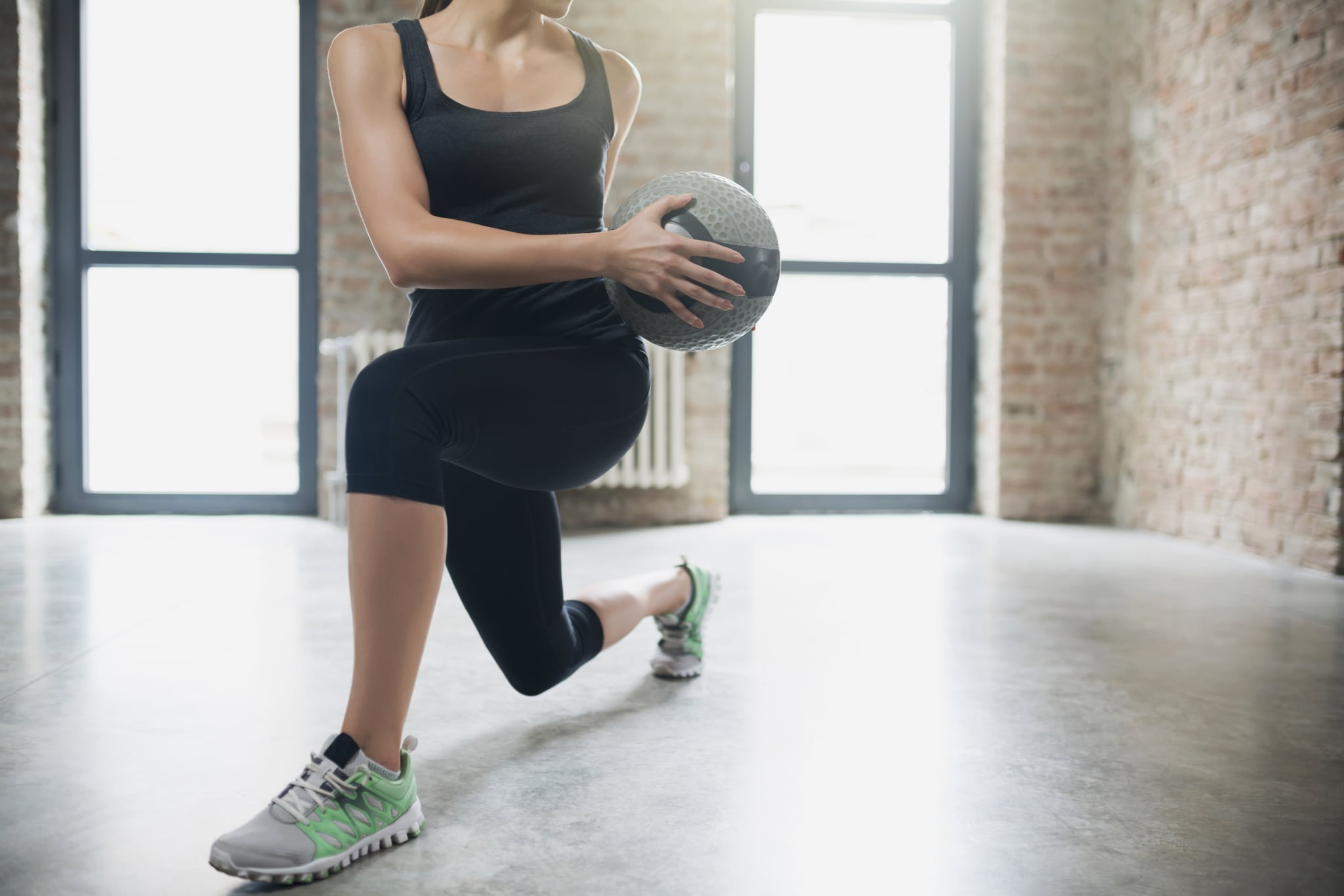 An unrecognisable young woman doing side lunges with medicine ball.
