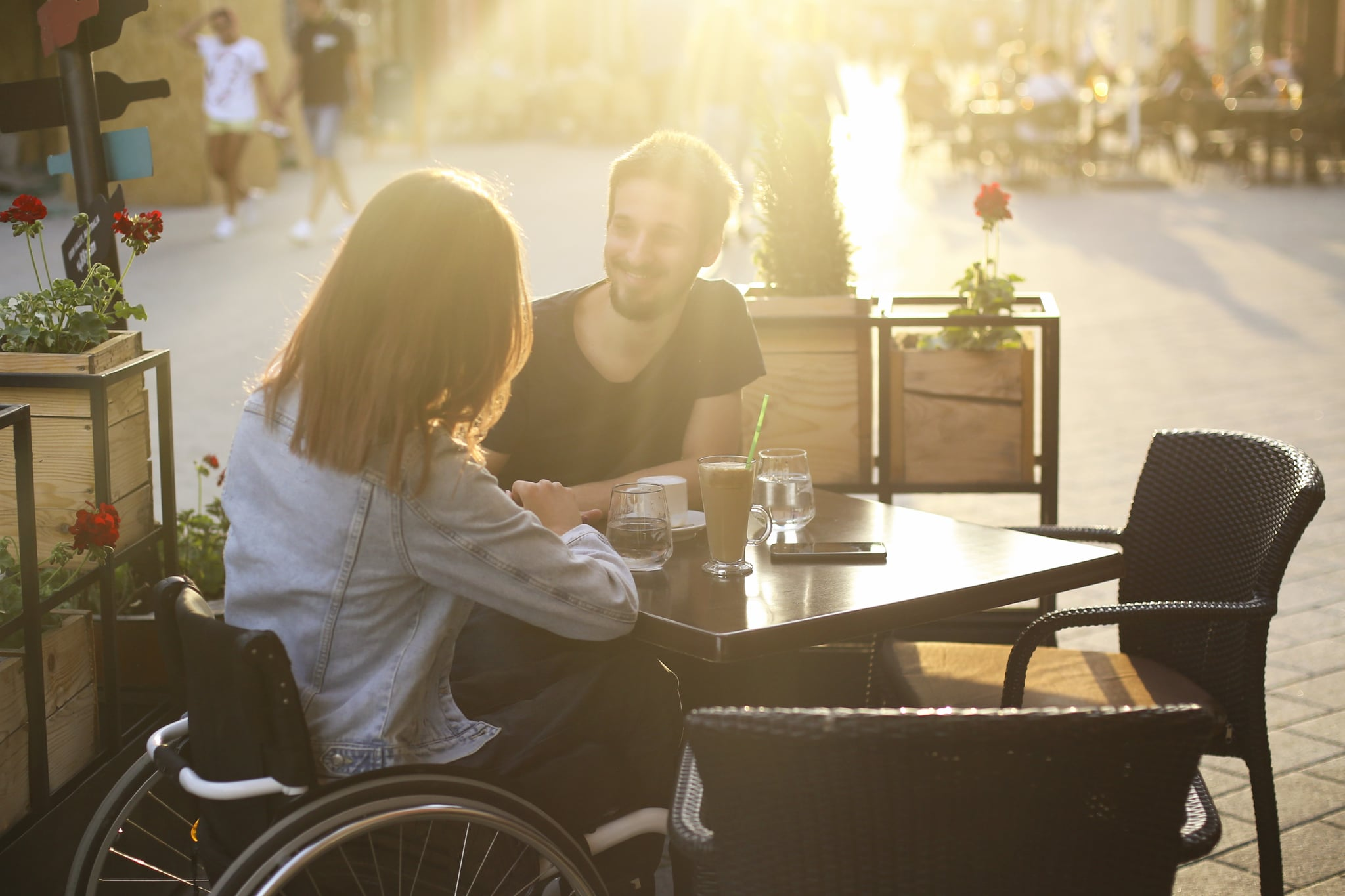 Disabled young woman and her boyfriend in a cafe. Both about 25 years old, Caucasian people.