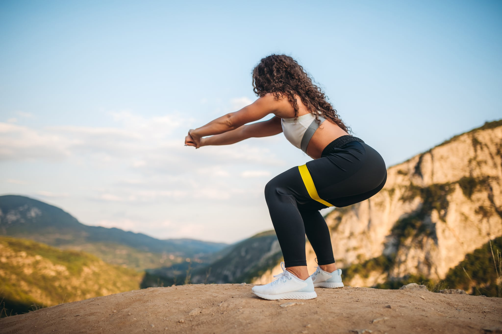 Young caucasian beautiful fit woman standing on top of a mountain and doing squats with resistance band.