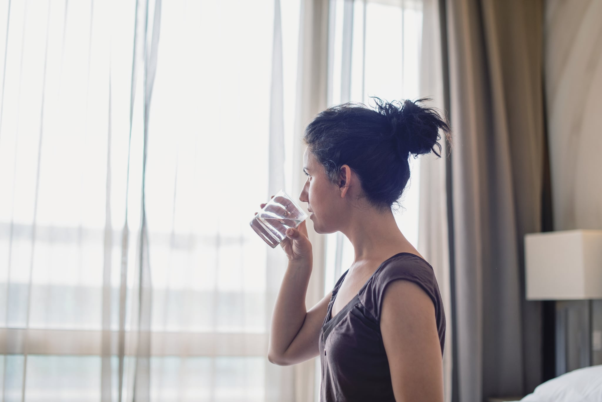 Young woman drinking water in the bedroom