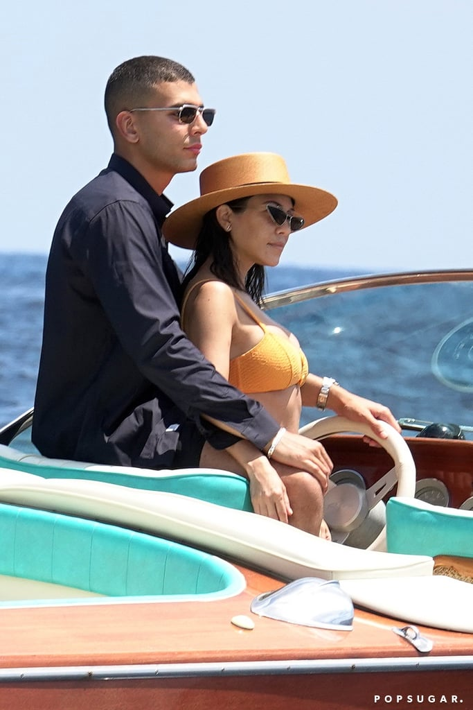 "Kourtney Kardashian and Younes Bendjima are living the good life! The couple is currently enjoying a romantic getaway in Italy, and on Friday, they were spotted soaking up the sun on a boat in Capri. The 39-year-old reality TV star and mother of three showed off her fit figure in a sexy orange bikini, while the 25-year-old model went shirtless and displayed his perfectly sculpted abs. OK, raise your hand if their trip is giving you major vacation envy!  Kourtney and Younes have been going strong since 2016, and the pair has also been documenting their trip getaway on Instagram. On Thursday, Kourtney posted a photo of herself in Rome, and the following day, Younes shared a video on his Instagram stories of Kourtney, captioning it, ""Teaching her la dolce vita."" Keep reading for a look at Kourtney and Younes's envy-inducing Italian vacation.       Related:                                                                                                           11 Photos of Kourtney Kardashian in Lingerie That Are So Hot, You'll Need to Call 911"