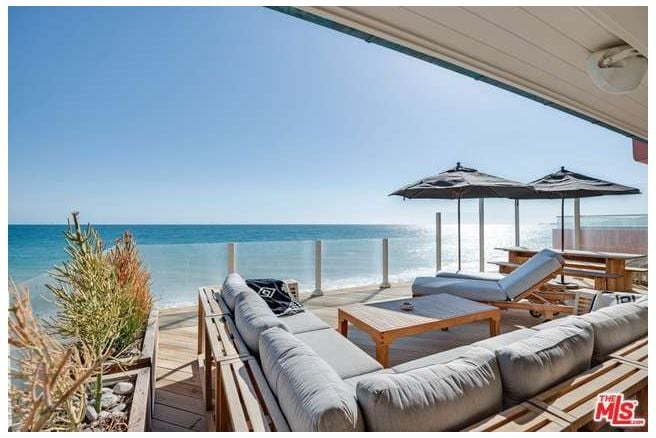 Leonardo DiCaprio is no stranger to real estate. He's dabbled in the industry, buying, renting out, and selling impressive properties. But his longest-term real estate relationship is poised to be his biggest win yet. The Oscar-winning actor just listed a Malibu beach house he purchased in 1998 for $2.12 million for a whopping $14.52 million. That's more almost seven times what he purchased the property for!  The three-bedroom, two-bath home is located on prestigious Carbon Beach and has undergone a stylish renovation between last year — when Leo rented it out for $30,000 to $66,000 per month — and today. The updated 537-metres-square cottage sits behind a gated entryway and welcomes guests into a gracious courtyard that leads to the unbeatable ocean-front location, complete with spectacular view.  While there's no pool, a hot tub sits on one of two wooden decks perched over the Pacific. Beachy light wood runs throughout the white-washed, open-concept interior, and a modernized kitchen features stylish grey tile and cabinetry. Check out the coveted Malibu property in the slideshow ahead.