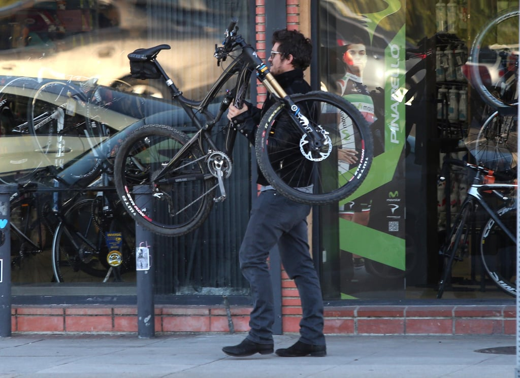 Orlando Bloom carried his bike into a bike shop.