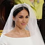 Meghan kept her five-meter-long wedding veil in place with a diamond-encrusted bandeau tiara, which originally belonged to Queen Mary and was lent to her for the special occasion.