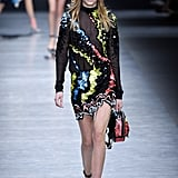 The sheer mockneck and sequined miniskirt debuted on the runway with patent leather ankle-strap heels and a matching backpack.