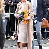 In New Zealand, Meghan covered a lighter-toned Brandon Maxwell dress with a classic Burberry trench.