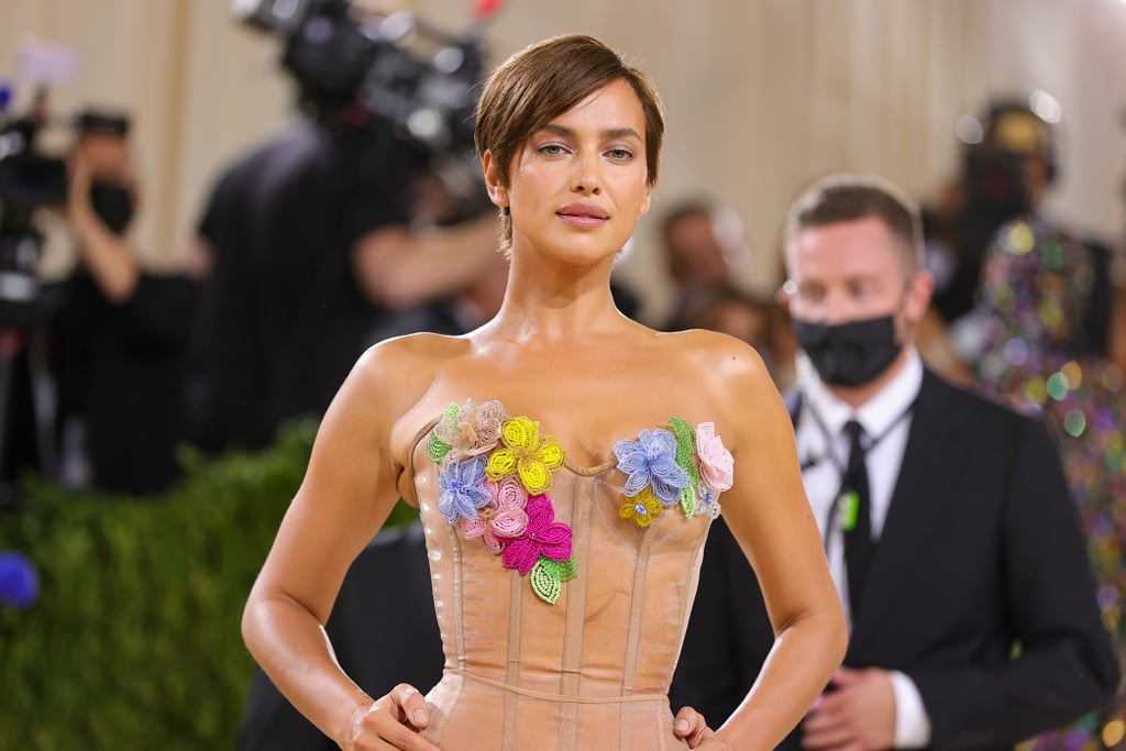 """Irina Shayk was full of surprises at Monday night's Met Gala. Known for her edgy street style and super-sleek bun, the model transformed into a flower girl for the event and casually debuted a fresh pixie cut in the process. While Shayk is often seen sporting the classic off-duty model look — long hair slicked back into a bun — her new hair is reminiscent of the '90s, particularly drawing inspiration from the iconic crop made famous by supermodel Linda Evangelista.  A huge chop is a big decision for some, but that didn't seem to be the case for Shayk. """"Something has to come dramatic to the Met Gala, and we decided it's about no makeup and fun hair, and here we go,"""" she shared on the red carpet, wearing a gorgeous Moschino creation adorned with flowers. She certainly brought the drama with her new pixie, cut and styled by celebrity hairstylist Harry Josh.  Ahead, get a closer look at the model's surprising hair transformation.       Related:                                                                                                           The Biggest Beauty Trend on the Met Gala Red Carpet This Year? Hair Structures"""