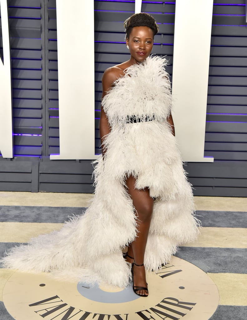 """We really hope Lupita Nyong'o isn't ticklish, because her feather-covered gown at the Oscars could give Tickle Me Elmo a run for his money. On Sunday night, the Black Panther actress donned a stunning Oscar de la Renta one-shoulder gown from the brand's Fall 2019 collection. While she didn't don Nakia's armor from the movie, Lupita paired the dress with Forevermark diamonds and absolutely shined on the huge night (Black Panther was nominated for seven Academy Awards). """"Light as a feather,"""" she captioned the dazzling Instagram photo. Welp, she just confirmed that angels exist in Hollywood! See more photos of Lupita's Oscar de la Renta gown at the Vanity Fair afterparty ahead.      Related:                                                                                                           The Party Doesn't Start Until You've Seen These Oscars Afterparty Dresses"""