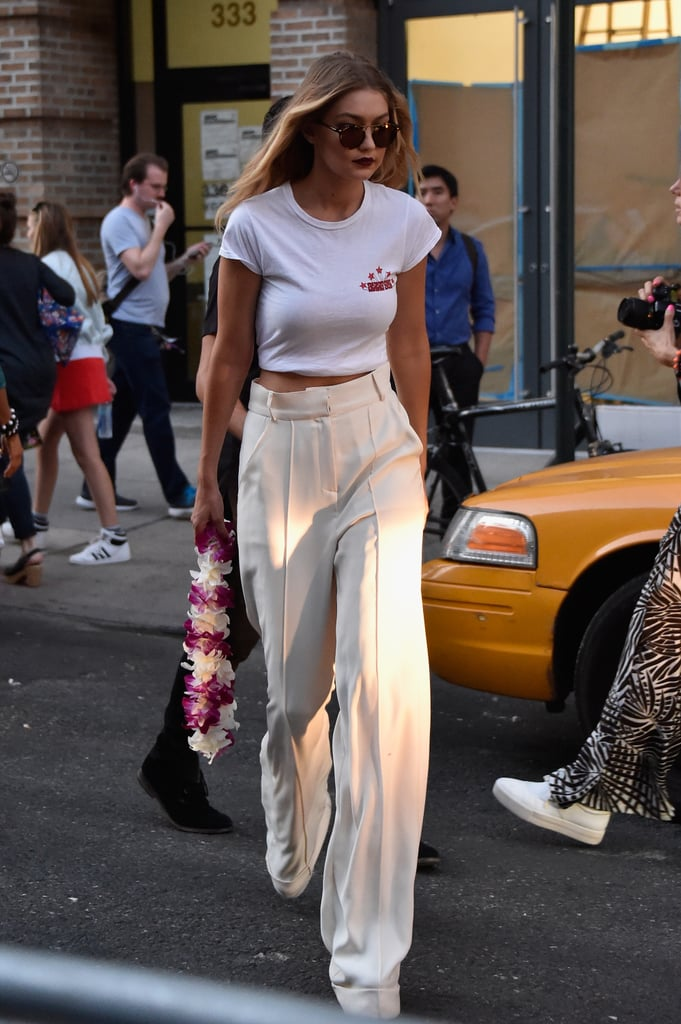 "Gigi hit the street in a cute white cropped tee, printed with ""Anna Sui"" on the front, cream wide-leg trousers, and round sunglasses. She held onto her lei — clearly the Anna Sui show was a luau with party favours!"