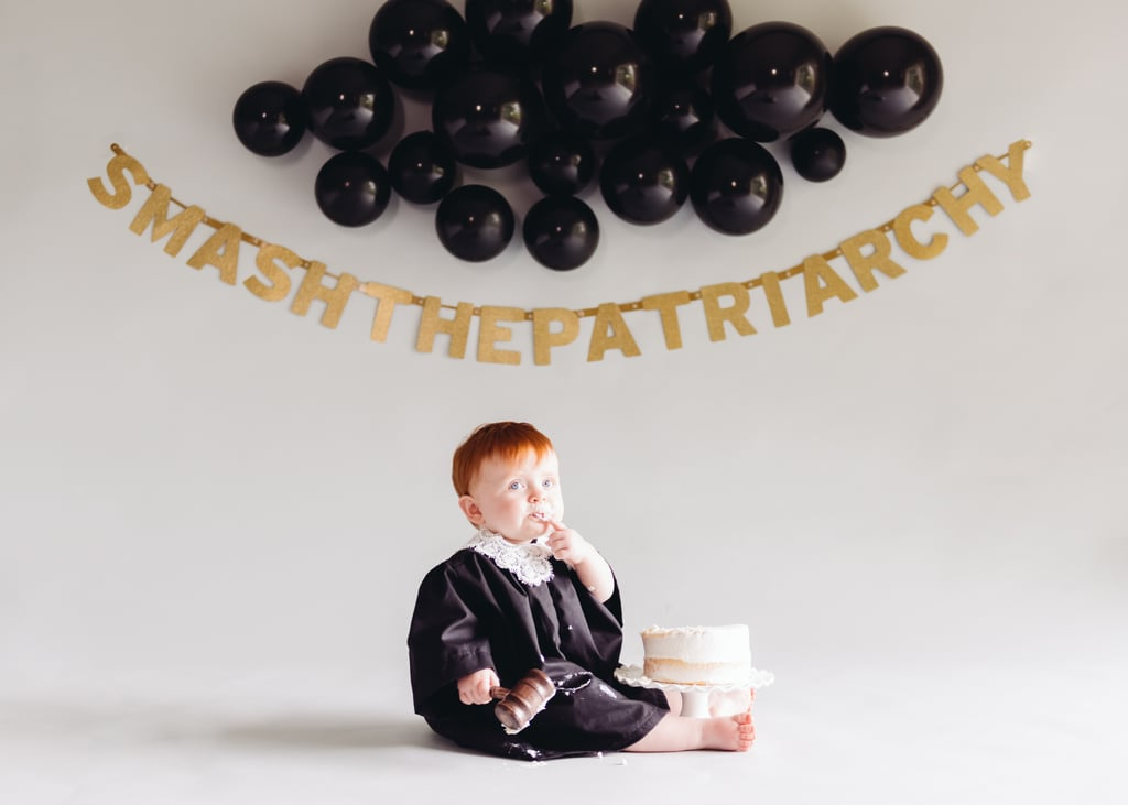"""Rachel Goodlad has always had a feeling that she'd have a daughter who she could raise to be a strong girl, and now that her daughter Charlotte Quinn — who everyone simply calls Quinn — has turned 1, she's helped her smash the patriarchy with an epic cake smash photo shoot. For the shoot, Rachel ordered Quinn a judge's gown and gavel from Etsy, and her photographer, Yvette from Yvette Michelle Portraits LLC, set up a backdrop of black balloons with a gold """"Smash the Patriarchy"""" banner. Quinn was plopped in front of it all, looking like a mini Ruth Bader Ginsburg, with a cake in crawl's reach. The results are absolutely incredible. Rachel told POPSUGAR: """"We have a 2-year-old son, and I explained to some of my friends that I really just want both of [my kids] to be awesome in whatever way they choose to be. The point that that is still a radical thing depending on what they choose to do and be, blows my mind. People focus on colors for baby products and the right types of toys and activities instead of just raising kind and amazing humans. I think there should be more focus on that and less on the stuff that doesn't matter. There is nothing wrong with being badass, and I hope neither my son or daughter shrink from who they were meant to be."""" Here, here! Ahead, check out all of the empowering photos from Quinn's first birthday cake smash shoot.      Related:                                                                                                           39 Smash Cake Ideas For Your 1-Year-Old's First Sugar High"""