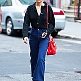 Selena kept it casual wearing a button-down black shirt, flared jeans, Stuart Weitzman boots, and her Coach bag.