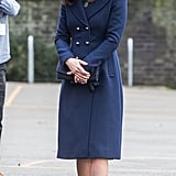For her visit to the Reach Academy with Place2Be, the duchess wore a long navy Hobbs coat with matching indigo gloves, a clutch, and a pair of suede Jimmy Choo pumps.
