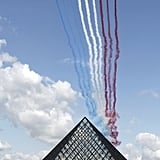 Jets shoot a blast of blue, white, and red over the Louvre Pyramid for Bastille Day.