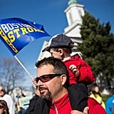 """A little boy sat on his father's shoulders holding a """"Boston strong"""" flag."""
