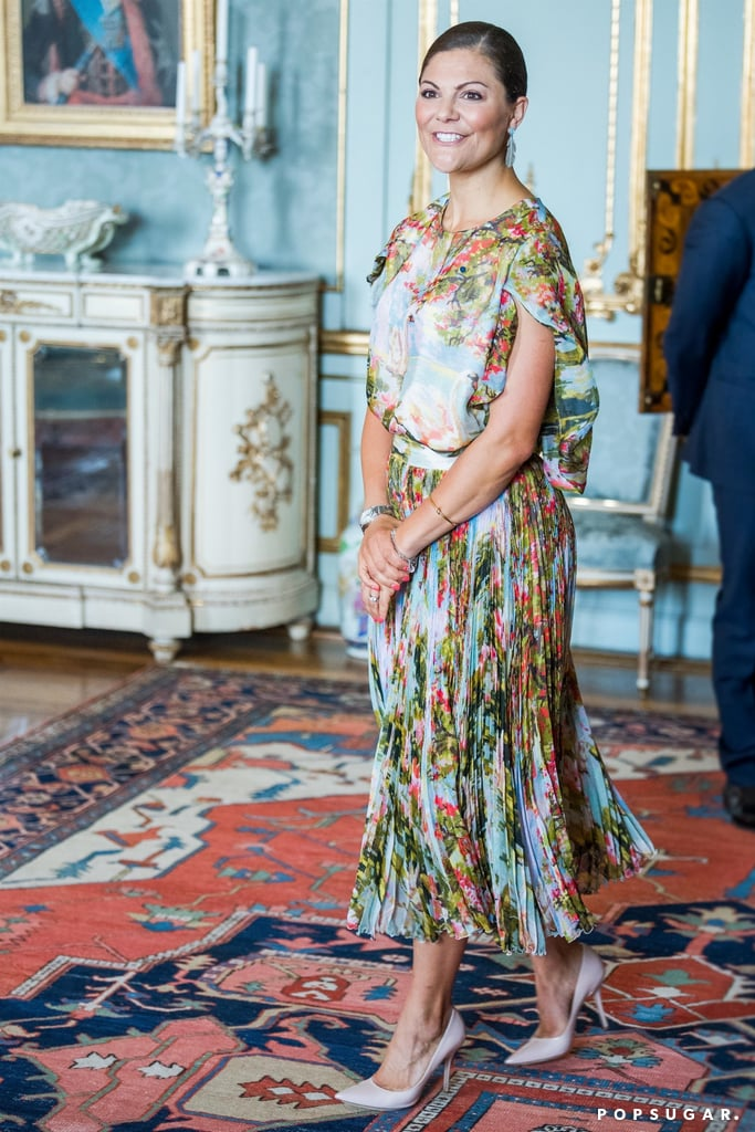For the royals, even a lunch date means dressing up in your finest. Princess Victoria of Sweden showed up to the Royal Palace wearing a Jennifer Blom dress that could only be described as a masterpiece. The ruffle cap sleeve ensemble fluttered as she walked and featured pleated details from the waist down. What was most stunning of all, however, was the dress's scenic print. Florals merged with blue skies, and there was even an image of a swan. The outfit practically resembled a beautiful impressionist painting you'd find on the walls of a museum. Princess Victoria kept the accessories to a minimum — just a few bracelets, a watch, and feather earrings — to let the dress really speak for itself. Of course, for the royal, this look is just one of many stunning outfits she has in her closet. Read ahead to see her dress from all angles, then shop similar picks below.      Related:                                                                                                           You'll Want to Zoom In on the Electric Blue Clutch Princess Victoria's Carrying