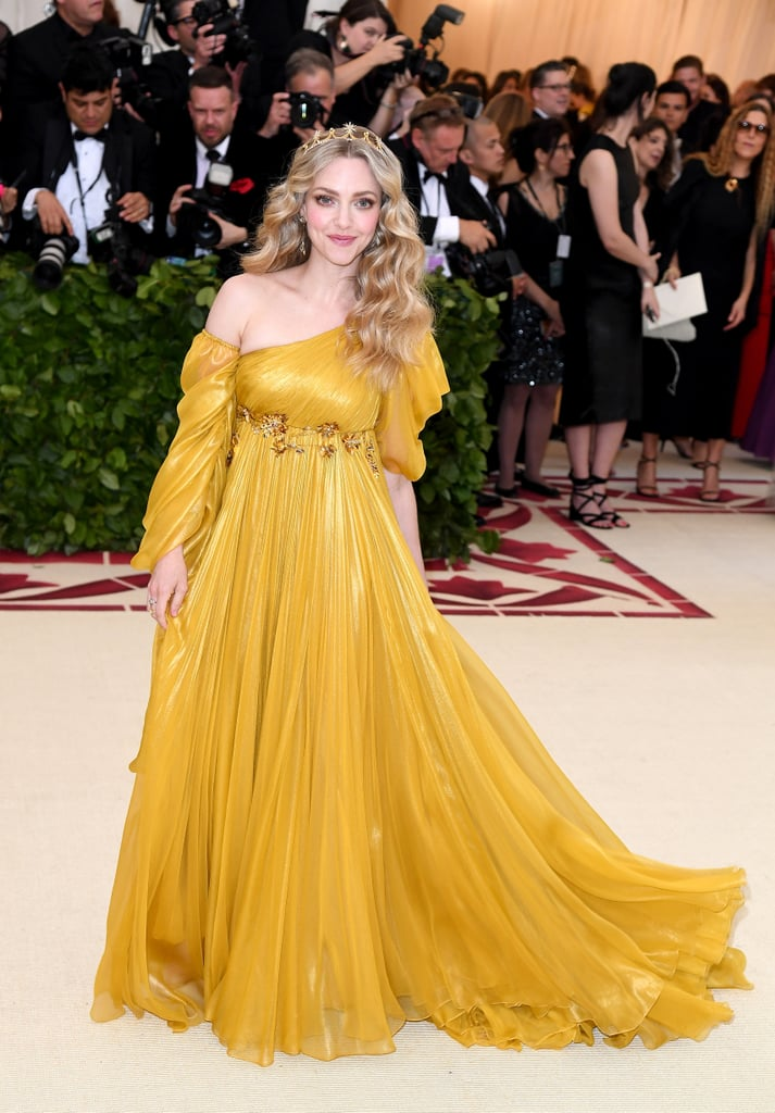 "Amanda Seyfried arrived at the 2018 Met Gala in a flowing gown fit for a glowing goddess. The 32-year-old actress adhered to the religious ""Heavenly Bodies"" theme by wearing a romantic Renaissance-style gown and tiara by Prada. Seyfried stuck so closely to the theme, in fact, that the shade of her gown is the specific shade of yellow used in the flag of Vatican City. She also turned the annual event into her own personal date night, posing for sweet pictures with her husband Thomas Sadoski all along the red carpet. Ahead, see pictures of Amanda's major Met Gala moment."