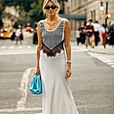 Camille Charriere brings a mixed material dress seem like an obvious choice for combatting summer heat with a bright blue clutch and thong sandal.