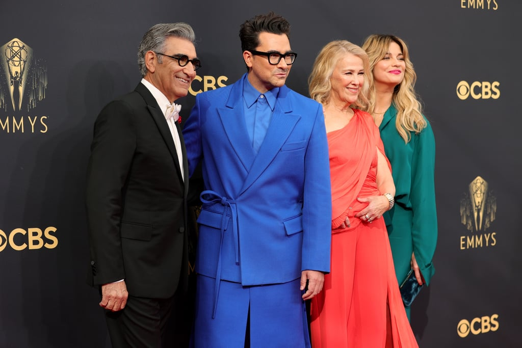Schitt's Creek may have come to an end, but it warms our heart to see the cast is still as tight as ever. On Sunday, Annie Murphy, Catherine O'Hara, and Eugene and Dan Levy had a sweet reunion at the Emmys in LA. The group exchanged smiles and held hands as they posed for photos together on the red carpet.  It was only last year that Schitt's Creek made history at the Emmys, taking home a whopping nine awards, which is the most won by a comedy in a single season. In addition to winning outstanding contemporary costumes, the show took home the award for outstanding comedy series, making it the first family sitcom to do so since Modern Family in 2014. This year, the gang was just kicking back and enjoying the show — see photos of their reunion ahead.