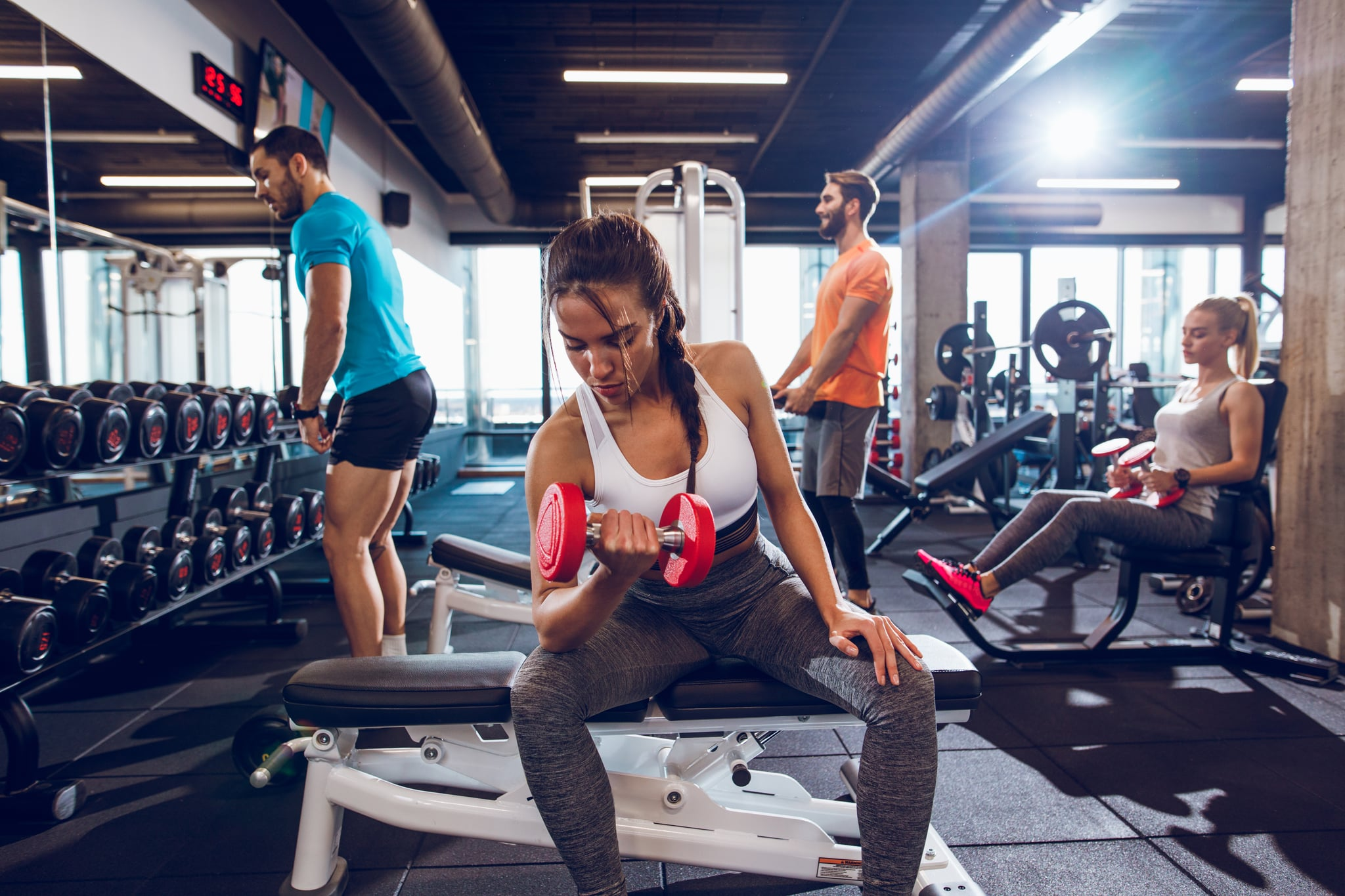 Young woman working out with dumbbells at gym