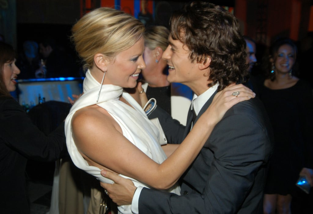 Charlize Theron grabbed ahold of Orlando Bloom at the GQ Men of the Year Awards in October 2003.