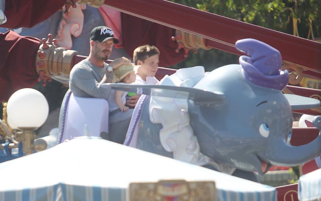 David Beckham held Harper Beckham while Brooklyn Beckham sat beside them on a ride at Disneyland.