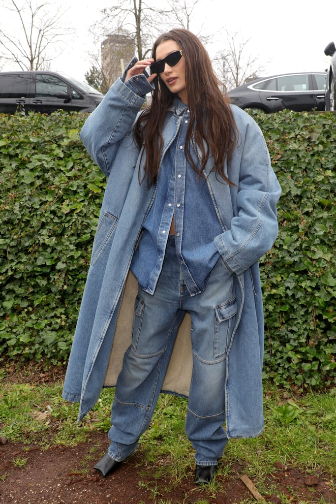 "No, you haven't traveled back in time and *NSYNC is not about to pop out of nowhere and break into a 2020 version of ""Bye, Bye, Bye."" But Bella Hadid is definitely making me feel like I've taken a trip back to the early aughts with the oversized denim-on-denim look she wore while attending the Balenciaga Womenswear Fall/Winter 2020/2021 show during Paris Fashion Week. As if one layer of jeans wasn't enough, Bella wore her coat open to reveal another denim shirt underneath and a beige crop top. So, yep, this is officially one of our favorite street style looks of the week. Britney Spears and Justin Timberlake made red carpet fashion history when they showed up at the 2001 American Music Awards in matching jean-clad outfits, and Bella's denim cargo pants and coat give off the same carelessly cool vibe. Bella paired the look with square-toed black boots and a pair of Balenciaga sunglasses. See her outfit from all angles and compare it to Justin and Britney's original looks ahead."