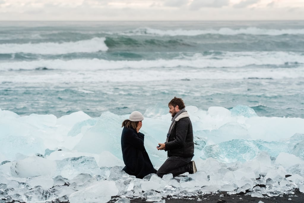 "Jökulsárlón glacial lagoon is known as the crown jewel of Iceland (even nicknamed ""diamond beach""), so what better place to propose to the love of your life with your own sparkling rock? In December 2018, Jonathan did exactly that and proposed to Ellen during sunrise in Jökulsárlón. The setting was stunning, taking place on a grand icy beach leading to the lagoon with the moon shining brightly in the blueish-orange sky.  With the weather constantly changing, previously drawn up locations might not work, so when Jonathan felt that it was the right time, he knelt down and popped the question. Photographer Mait Jüriado was there to capture the happy couple on their big day. ""You just feel it's the right time! That's just how it went for Jonathan and Ellen too, as we didn't plan this epic sunrise in Iceland or the lagoon with spectacular ice – it just happened and it was perfect,"" said Mait. ""There's no need to worry about missing the 'right' moment, it's not worth the trouble because we will have so many more magical moments and places on our journey than you can ever imagine."" Keep reading to see all the beautiful photos from the spectacular day, including the pair's exploration of blue ice caves that feature centuries-old ice — a once-in-a-lifetime experience as these caves evolve yearly due to rock erosion. Prepare to lose yourself in this otherworldly proposal!"