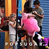 Pax snacked on a sweet while Zahara collected a large stuffed animal at a canival game.
