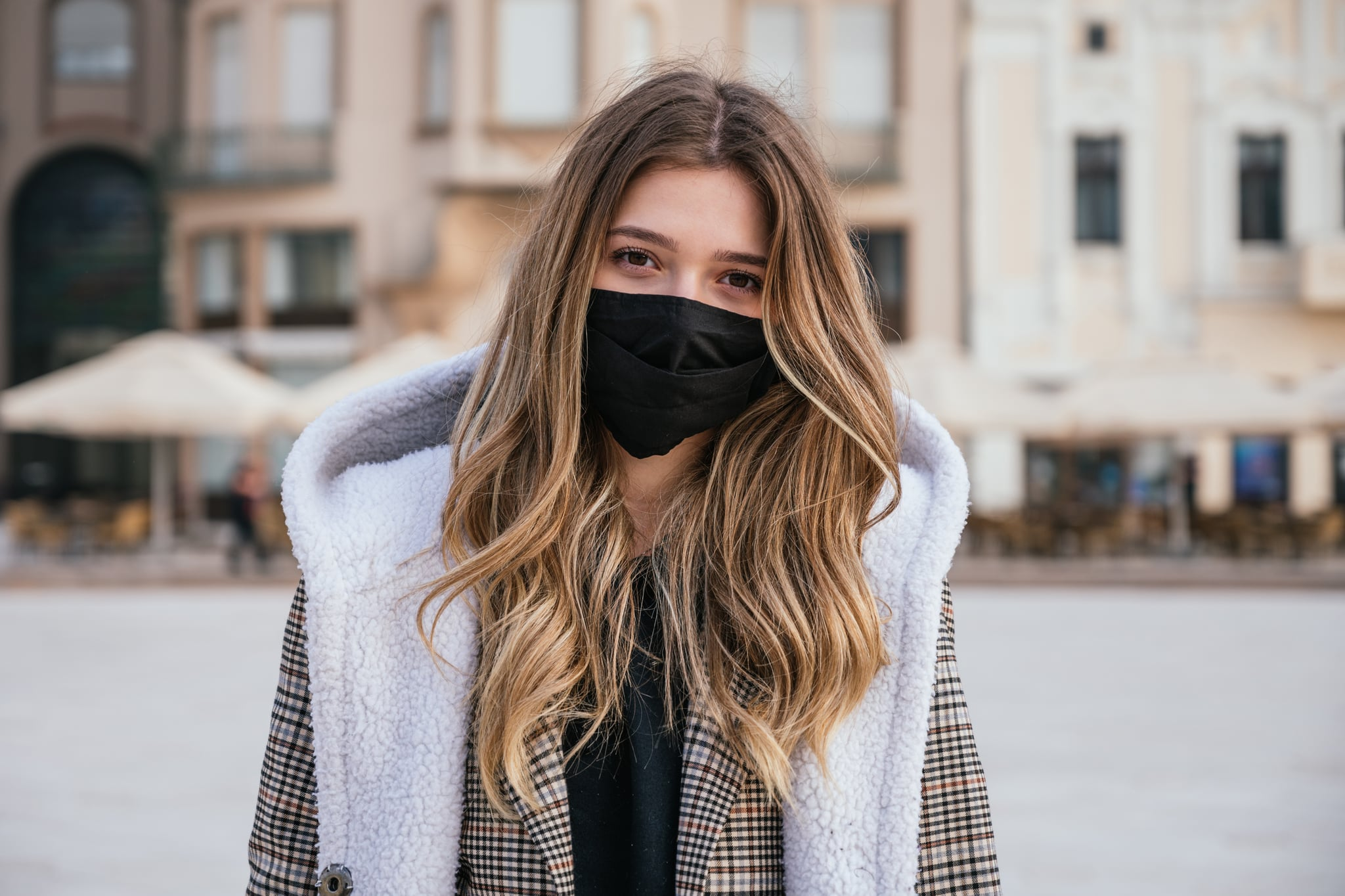 Portrait of a young woman wearing mask and winter clothes