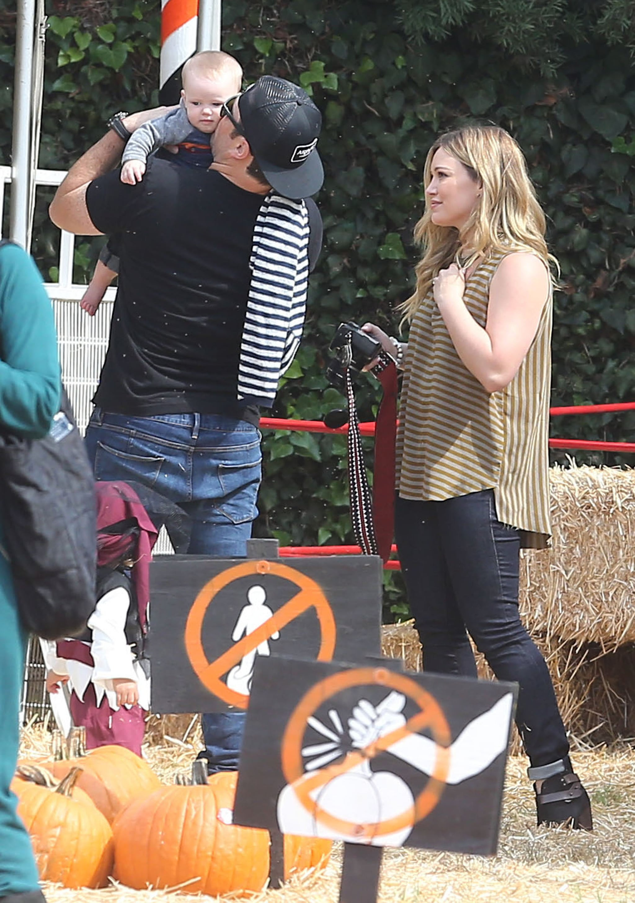 Hilary Duff looked adoringly at her little one, Luca, as dad Mike Comrie gave him a kiss at Mr. Bones Pumpkin Patch in LA.