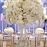 Touches of gold and crystal, combined with purple uplighting, make these all-white centerpieces anything but boring.