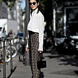 Caroline Issa remixes traditional trousers and a pretty blouse, just by adding a touch of the trends.