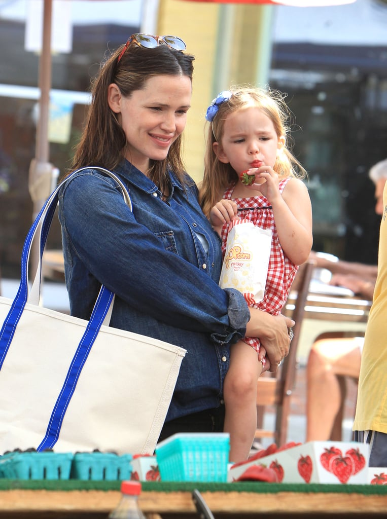 Jennifer Garner carried a snack-eating Seraphina Affleck through the farmers market in LA in May 2012.