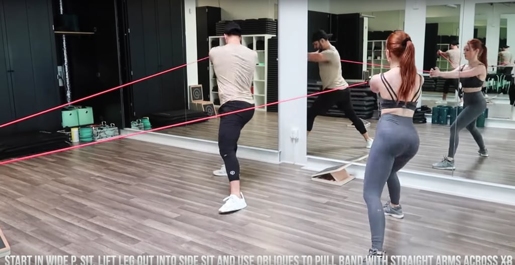Now for some abs. Start in a wide squat stance, lift one leg out into a side squat, and use your oblique muscles to pull the band across your body, keeping your arms straight.