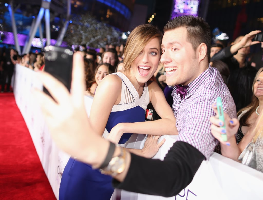 While walking the People's Choice Awards red carpet, several Hollywood stars stopped to pose for pictures with fans. Allison Williams gave a big smile for one fan while leaning in for a photo, while other celebrities like Jessica Alba, Heidi Klum and Miles Teller also joined in on the selfie fun. As for Nina Dobrev and Bailee Madison, they took matters into their own hands to snap pictures with fans. See all the best fan selfies from the People's Choice Awards!