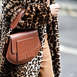 Style Your Leopard-Print Coat With: A Sleek Brown Bag and Tan Pants