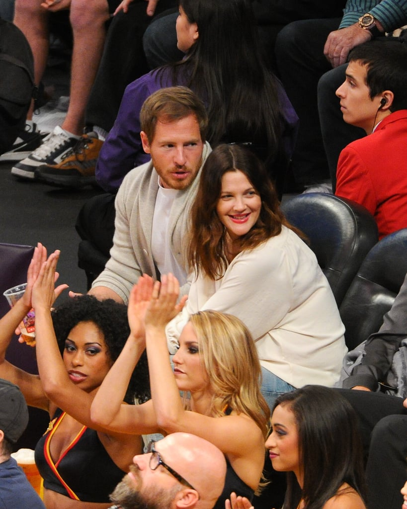 Drew Barrymore and husband Will Kopelman had prime seats to watch the LA Lakers take on the LA Clippers at the Staples Center on Friday evening. The duo sipped on beers and checked out the halftime dancers just a few feet away. It was the latest low-key date night for the new parents, who welcomed daughter Olive to the world in September. We've yet to see the little one, though Drew and Will have been able to squeeze in some romantic outings together. Drew is reportedly also working on a makeup line for Walmart set to launch in early 2013, so she's not slowing down careerwise either.