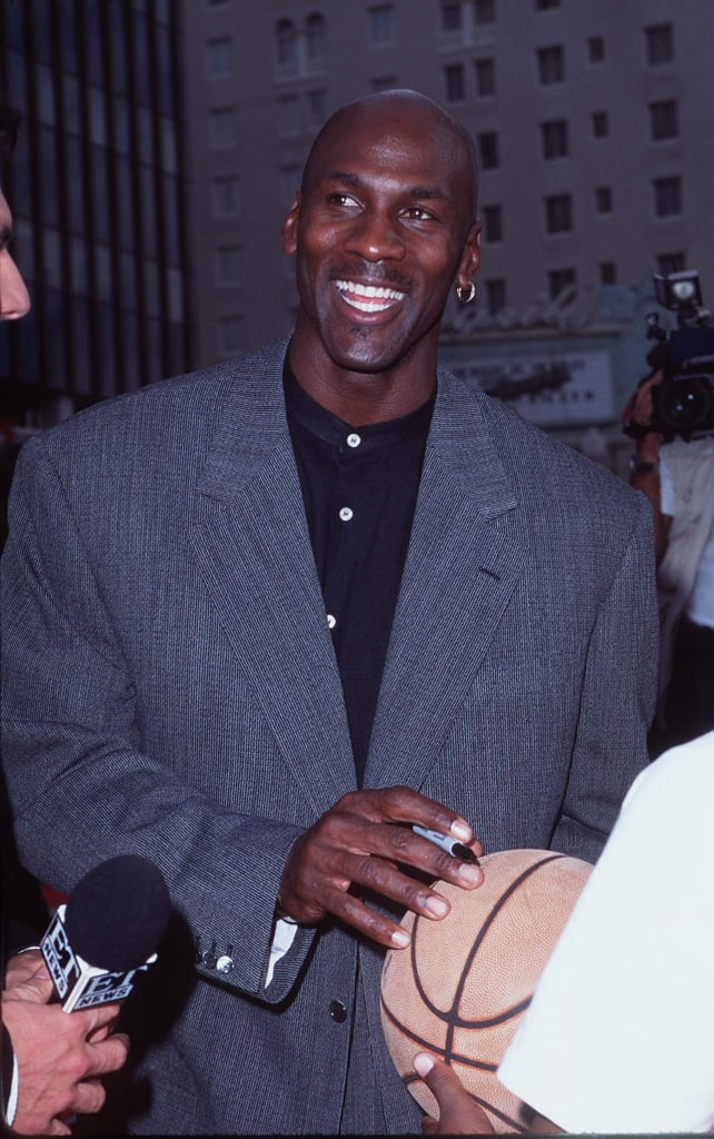 Michael wore a gray blazer with a mandarin-collar button-up shirt and his signature single earring to the premiere of Space Jam in Los Angeles in 1996.
