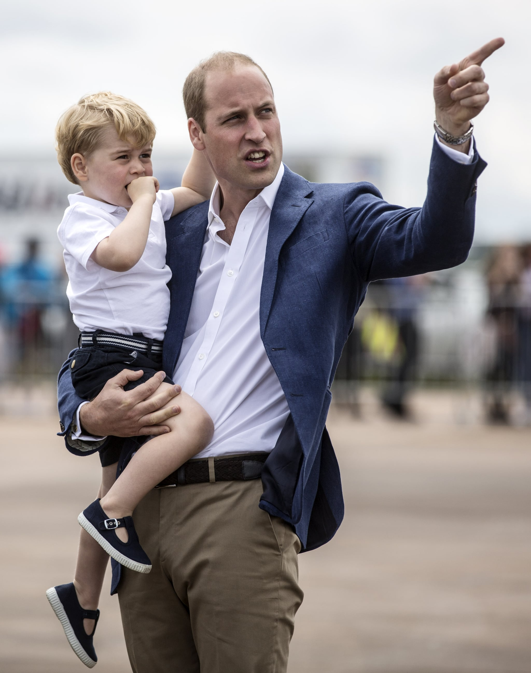 Britain's Prince George is carried by his father Prince William as they visit the Royal International Air Tattoo at RAF Fairford in western England, on July 8, 2016. / AFP / POOL / RICHARD POHLE        (Photo credit should read RICHARD POHLE/AFP/Getty Images)