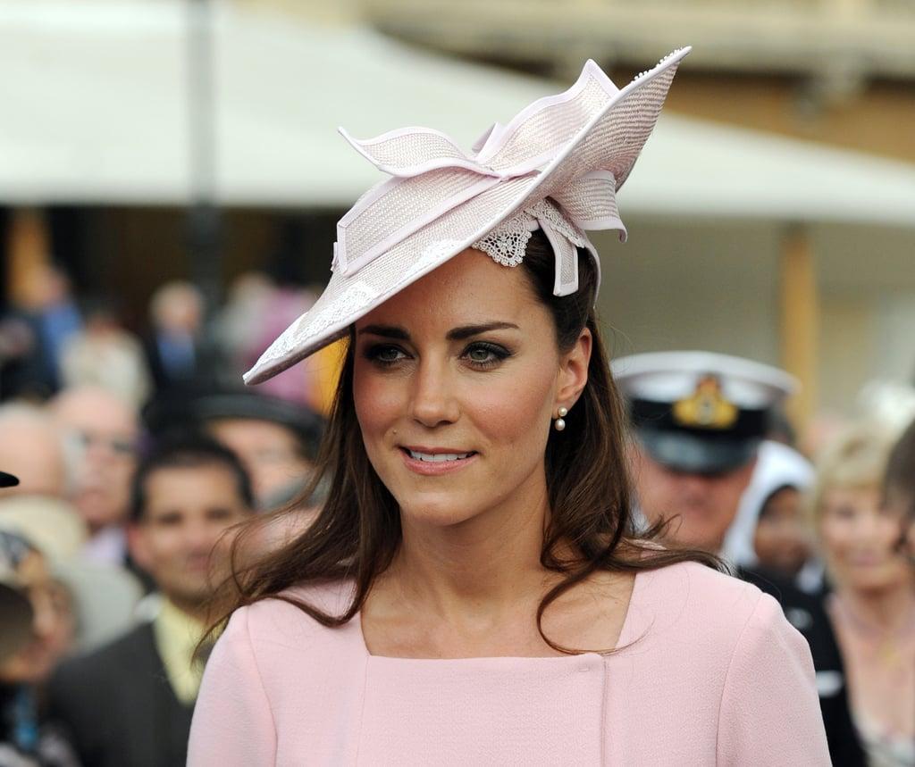 كانت قبّعة كيت الورديّة التي صمّمتها جين كوربيت تتناسب بشكلٍ مثاليٍّ مع فستانها من علامة إميليا ويكستيد الذي ارتدته في حفلة أقيمت بحديقة قصر باكنغهام عام 2012.