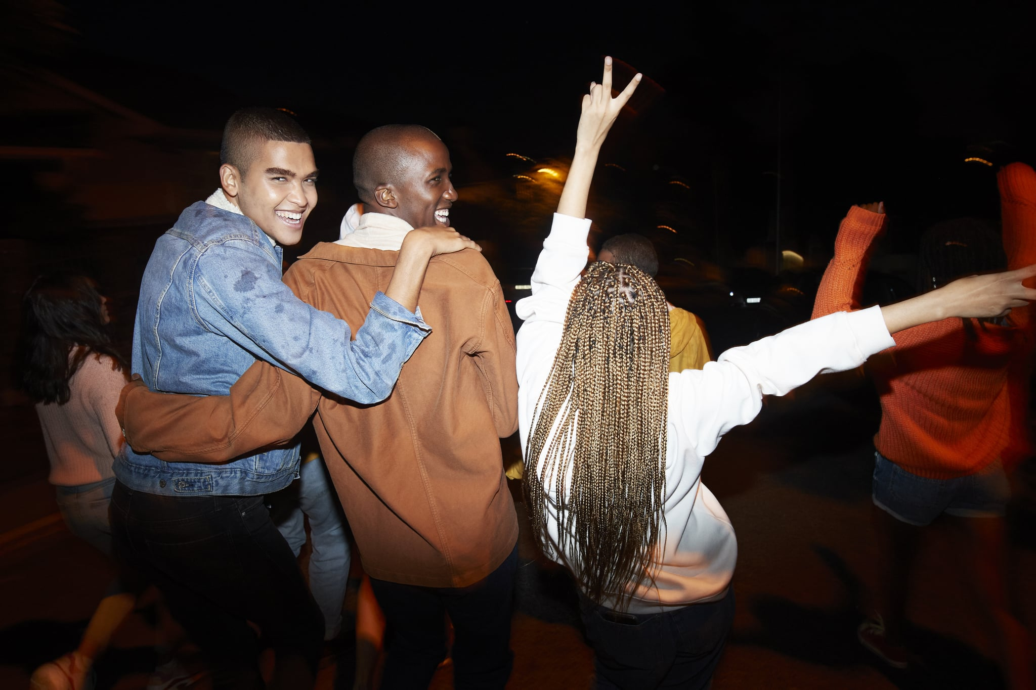 Cheerful young males dancing with multi-ethnic friends at night
