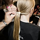 Step 4: Tease the base of your ponytail, then slip a belt over the elastics, or wrap a ribbon around them, making sure that one end hangs lower than the other.