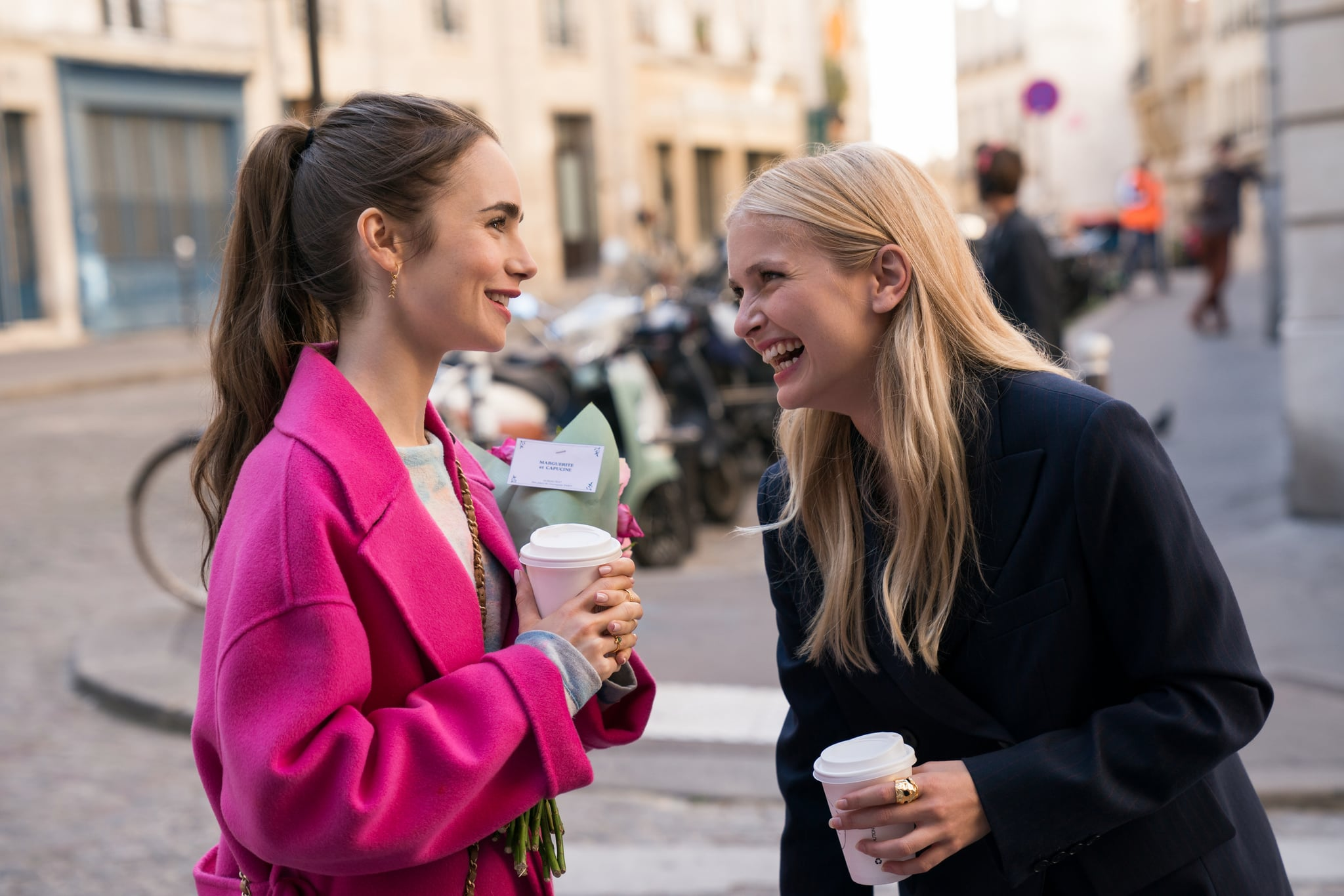EMILY IN PARIS (L to R) LILY COLLINS as EMILY and CAMILLE RAZAT as CAMILLE in episode 104 of EMILY IN PARIS. Cr. STEPHANIE BRANCHU/NETFLIX  2020