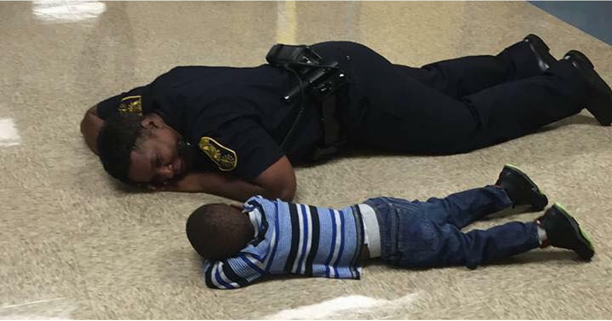 photo of police officer lying down with little boy