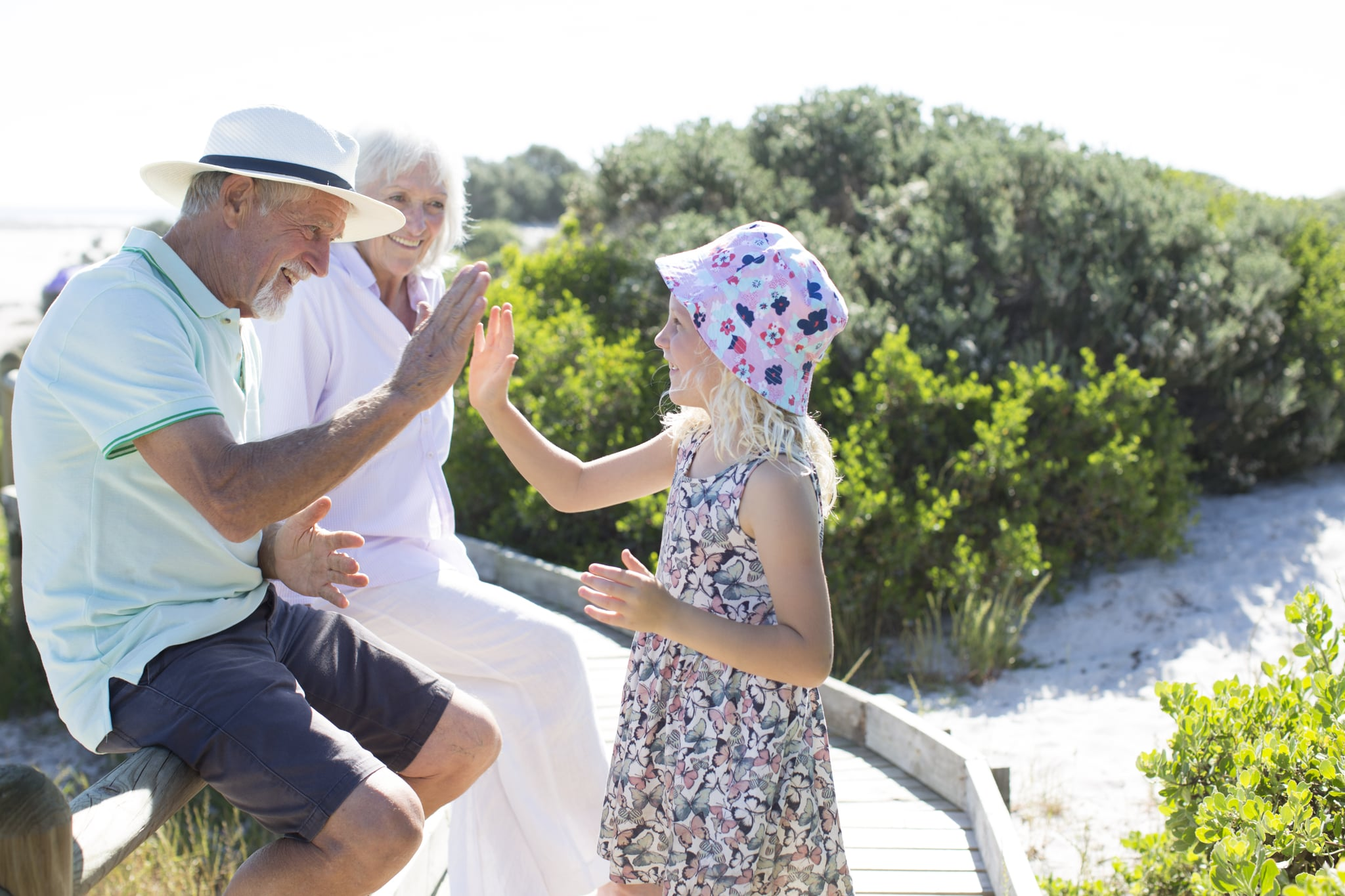 Senior couple, aged 70-75, playing outdoors with their grandchildren